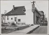 [Bakery and laundry near storefront of old residence, south side of West 23rd Street, west of Union Avenue]