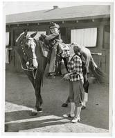 Young boy, Tim Turner, dressed as a cowboy on horseback with a woman, Mrs. John Zafferano, looking on