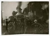 R.E. Dunn and other fire fighter with steam pump engine, September 12, 1912