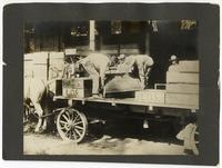 Agricultural laborers unloading boxes of raisins in Selma, Fresno County, California