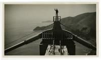 Golden Gate Bridge construction, man waving atop completed north tower