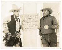 Ranchers in front of sign