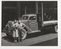 Woman, man, and cat in produce market, Washington Street, San Francisco