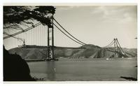 Golden Gate Bridge construction, view from east of Fort Point during raising of roadway