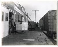 Loading boxes of Sylmar Brand olive oil onto freight cars at the Olive Grower's Association, Los Angeles, California
