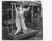 Butcher and butchered pigs in front of meat market, Fillmore Street, San Francisco