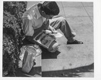 Man eating a sandwich while reading a comic book, San Francisco