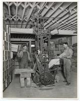 Workers using a machine to make boxes