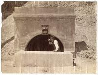 Man standing at entrance to Bear Valley irrigation system tunnel no. 1