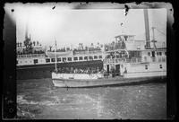 Troops aboard steamship departing for Philippines, with ferryboat Herald in foreground, San Francisco Bay