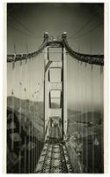 Golden Gate Bridge construction workers painting suspender ropes above completed roadway