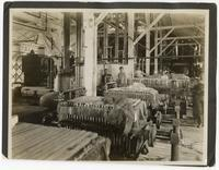 Men standing at the filter presses used for processing beet sugar, California