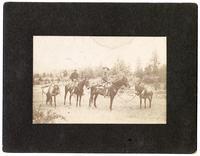 Armed cowboys on horseback